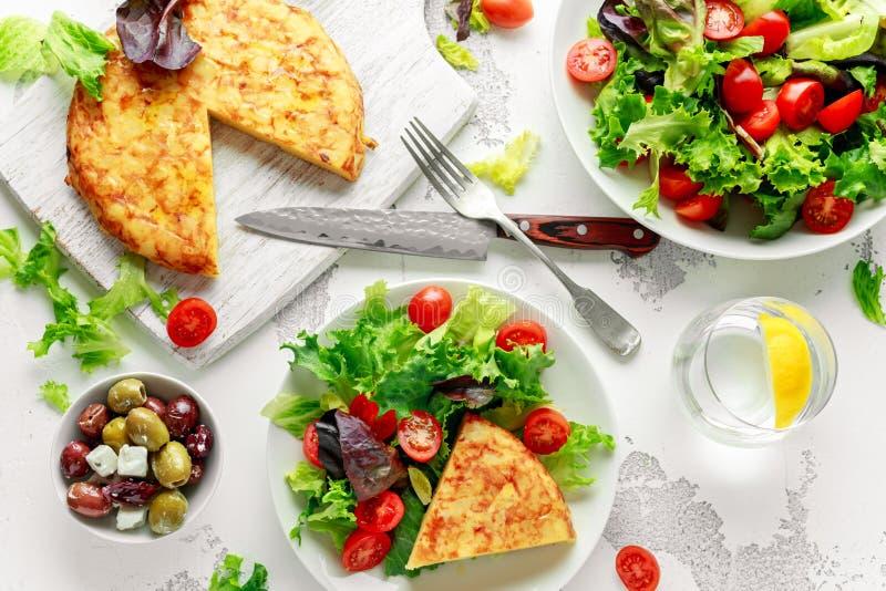 Spanische Tortilla, Omelett mit Kartoffel, Zwiebel, Gemüse, Tomaten, Oliven und Kräuter in einer weißen Platte Frühstück lizenzfreie stockfotos