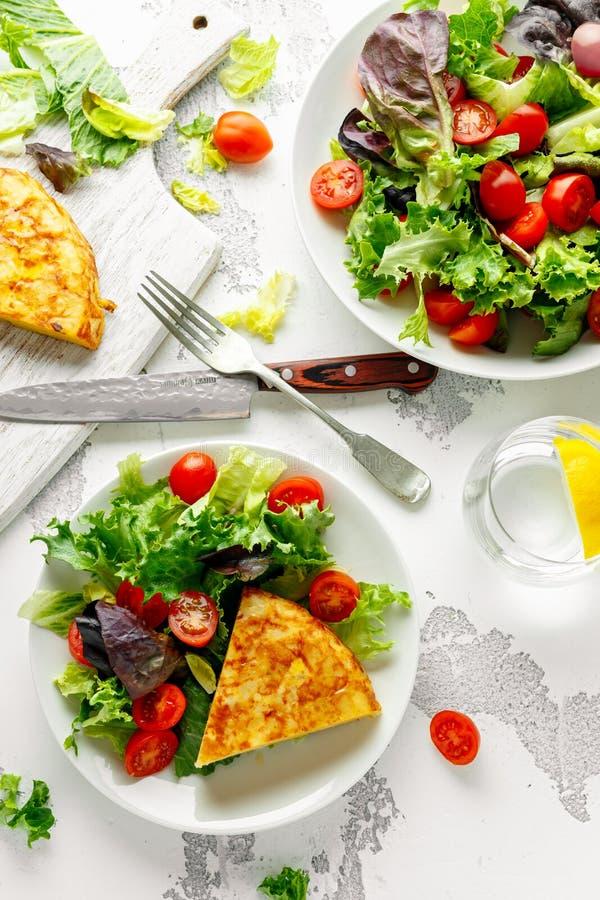 Spanische Tortilla, Omelett mit Kartoffel, Zwiebel, Gemüse, Tomaten, Oliven und Kräuter in einer weißen Platte Frühstück stockbild