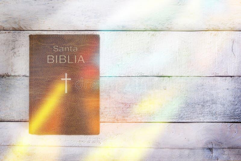 Spanische Version der heiligen Bibel mit irgendeiner Buntglasreflexion auf einem Holztisch Draufsicht und leerer Kopienraum lizenzfreie stockfotos