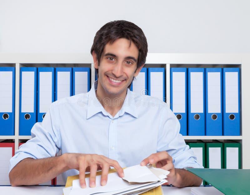 Spanischer Kerl im Büro, das Briefe sortiert lizenzfreie stockfotografie