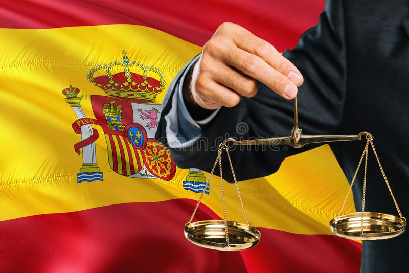Spanischer Richter hält goldene Skalen von Gerechtigkeit mit wellenartig bewegendem Flaggenhintergrund Spaniens Gleichheitsthema  lizenzfreies stockbild
