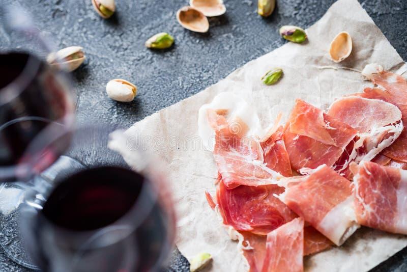 Spanisches Schinken jamon serrano oder italienisches Prosciutto crudo, Gläser Rotwein und Pistazien stockfotos