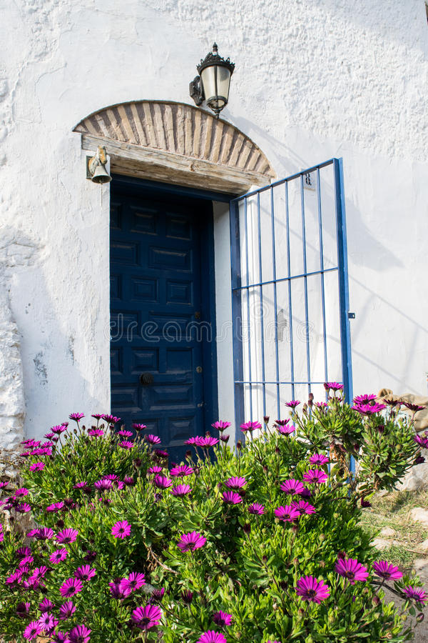 Spanish blue old entrance door with the open gate in white house stock photo