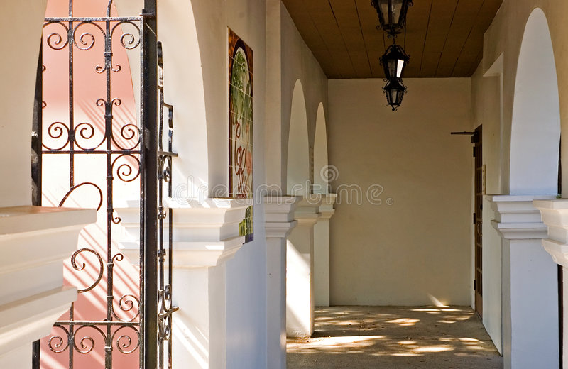 Spanish Breezeway. A view down a breezeway or walkway with archways and an elaborate wrought iron door between to Spanish buildings in historic St. Augustine stock photos