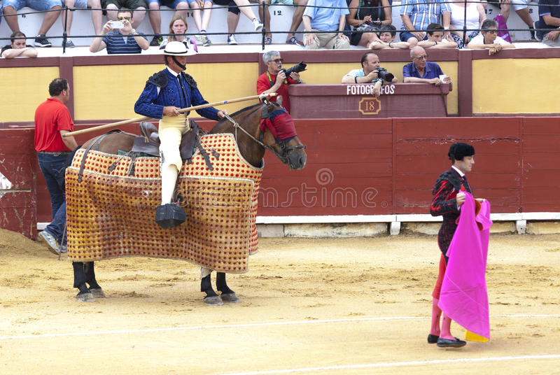 Spanish bullfight. Picador with a spear on a horse.The enraged bull attacks the bullfighter. Spain 2017 07.25.2017. Vinaros Monume royalty free stock photo