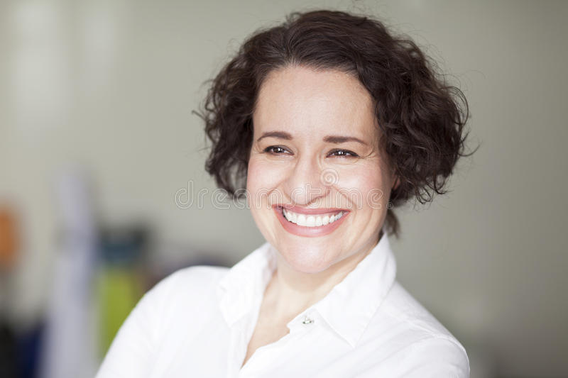 Spanish Businesswoman Smiling At the Camera. At the office. stock photography