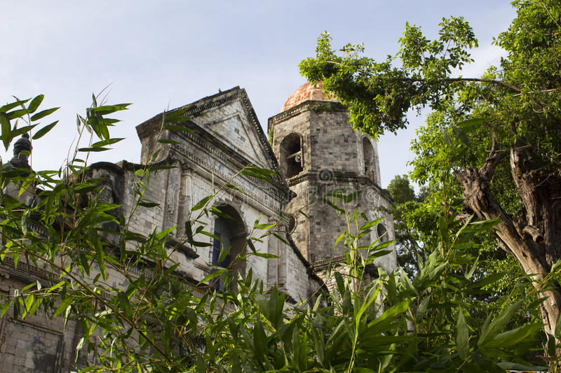 Spanish church dome in gothic style beneath green trees stock photo