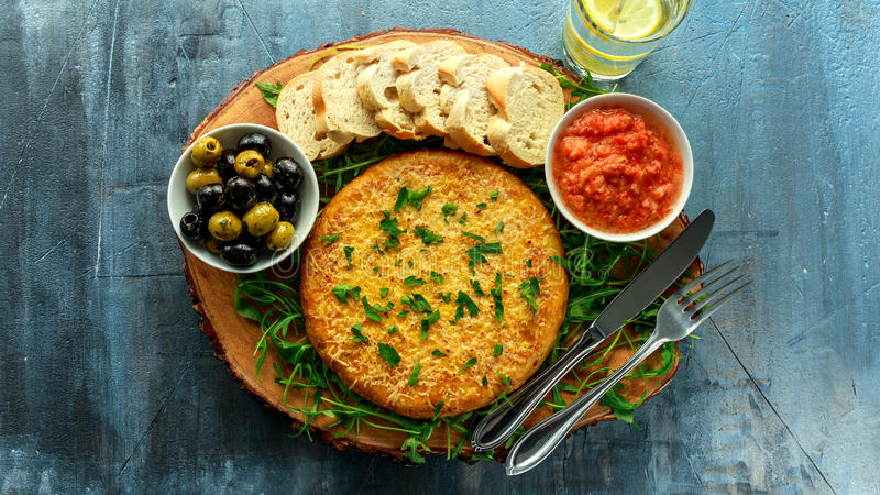 Spanish classic tortilla with potatoes, olives, tomatoes, rucola, bread and herbs. royalty free stock photography