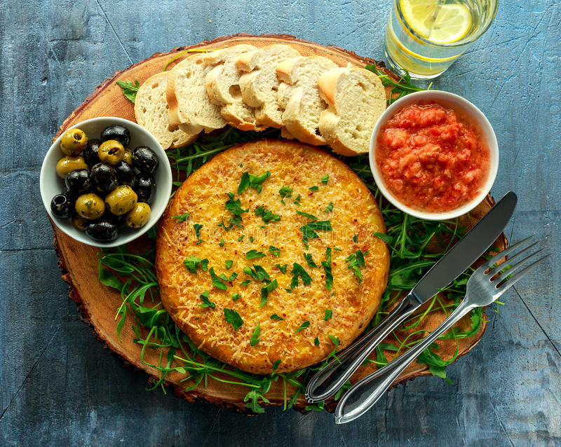 Spanish classic tortilla with potatoes, olives, tomatoes, rucola, bread and herbs. royalty free stock photo