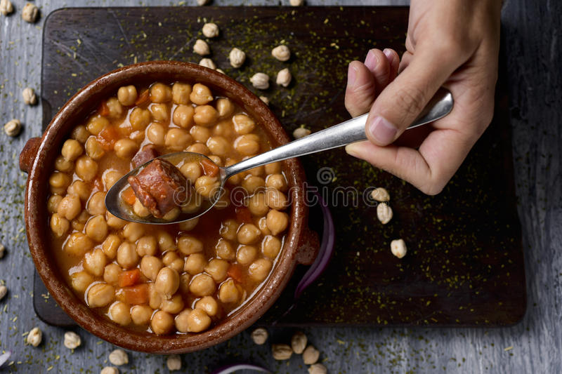 Spanish cocido madrileno, stew typical of madrid. High-angle shot of the hand of a man with a spoon and an earthenware bowl with spanish cocido madrileno, a stew stock photos