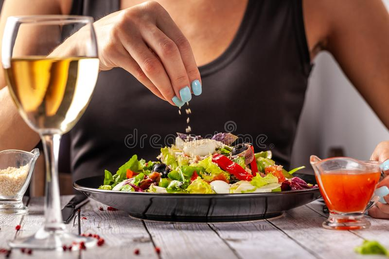Spanish cuisine. Mixed salad fish salad, red and green Bulgarian pepper, quail eggs, canned mackerel, olives, seasoned with oil royalty free stock photos