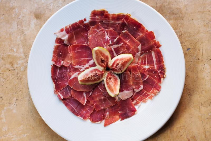 Spanish Cuisine tapas food Jamon serrano with fig. Beautiful appetite slices of raw pork meat, white plate background stock photo