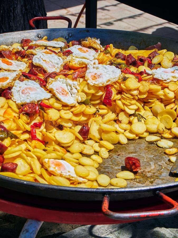 Spanish eggs with chorizo, potatoes and peppers to the frying pan. Spanish eggs. Fried eggs with chorizo, potatoes and peppers to the frying pan. Spanish street royalty free stock photos