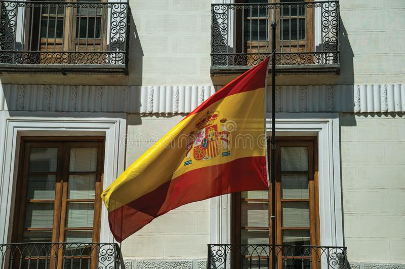 Spanish flag fluttering in front of building facade in Madrid stock images