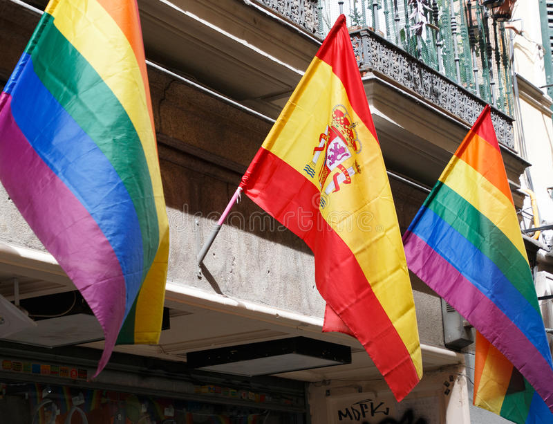Spanish flag with Wold pride flags. Pride flags flanking a flag of Spain stock photo
