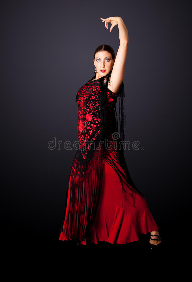 Spanish Flamenco dancer. Beautiful female Spanish Flamenco dancer doing a typical line pose, wearing modern attire. Spanish woman dancing Paso Doble in red and stock images