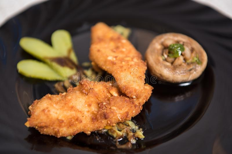 Spanish food, tapa finger chicken and mushroom on black plate. Close up photography royalty free stock photo
