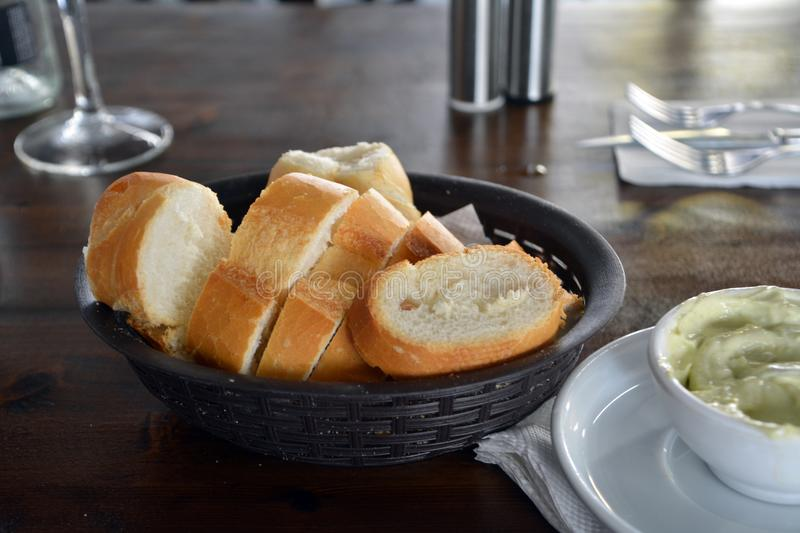 Spanish fresh bread on a basket on a restaurant table. Fresh bread sliced and decorated on a basket on a restaurant table royalty free stock photography