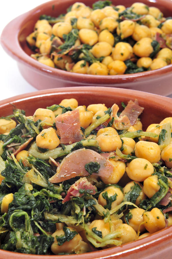 Spanish garbanzos con jamon, chickpeas with serrano ham, served. Closeup of a plate with spanish garbanzos con jamon, chickpeas with serrano ham, served as tapas royalty free stock images