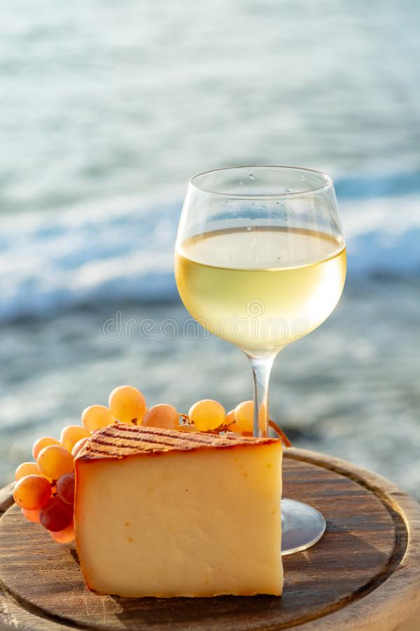 Spanish goat milk cheese with paprika coating and ripe pink table grapes served with white wine on outdoor terrace. Close up royalty free stock photo