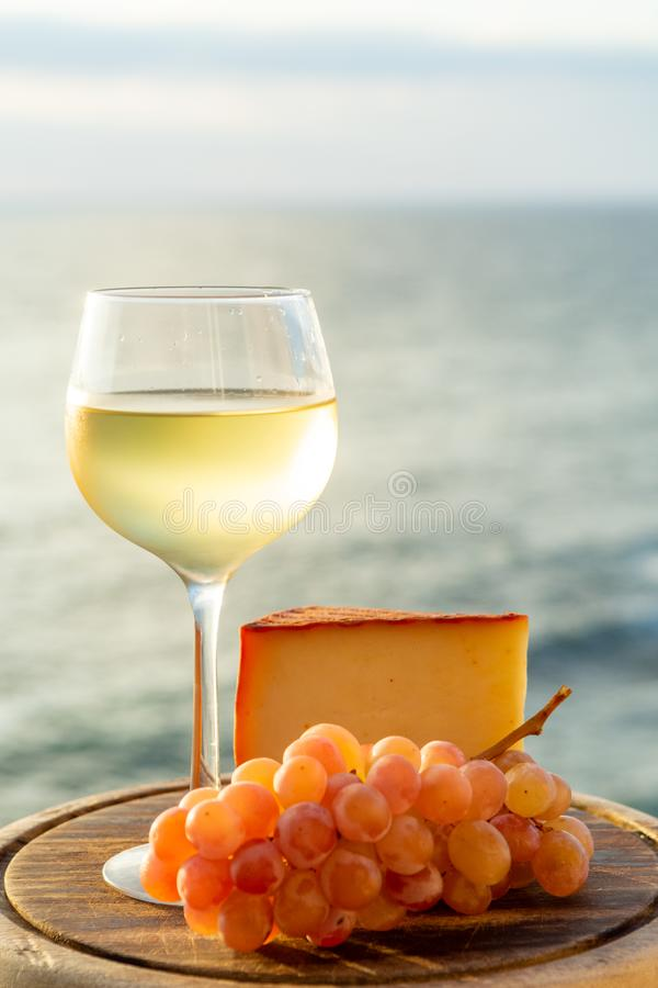 Spanish goat milk cheese with paprika coating and ripe pink table grapes served with white wine on outdoor terrace. Close up stock image