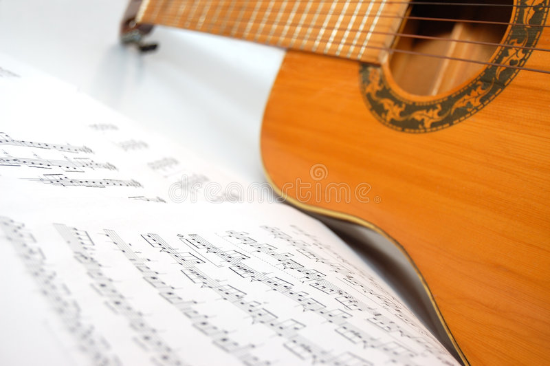 Spanish guitar and notes. Spanish guitar and paper leaves with notes stock photo