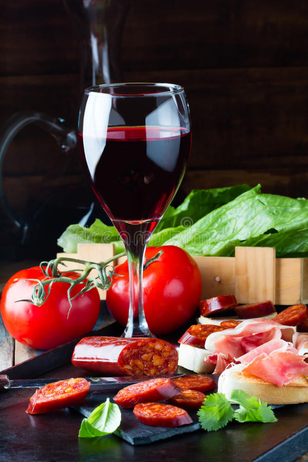 Spanish ham, salami and glass of res wine. Jamon Serrano. Ham Serrano and salami with bread accompanied by glass of red wine royalty free stock photography