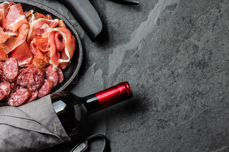 Spanish ham serrano, salami and bottle of red wine on slate. Background, top view royalty free stock photo