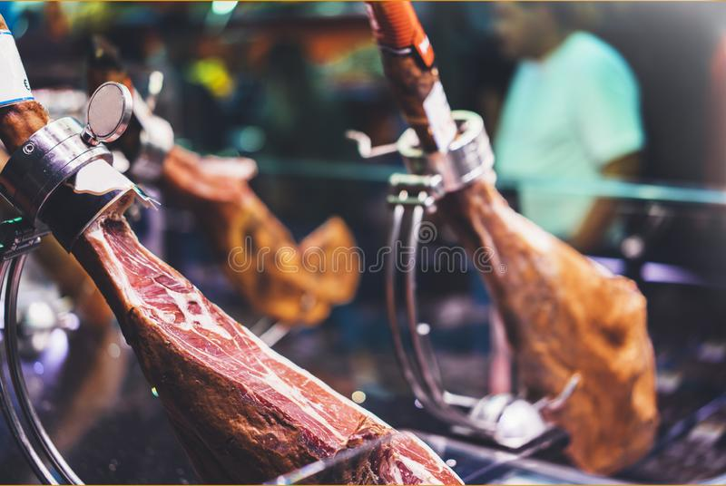Spanish hamon in barcelona market, jamon iberico in view black leg pork , traditional national spain meat in store, serran. O prosciutto food on background royalty free stock images