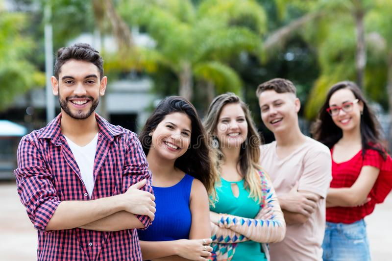 Spanish hipster man with male and female young adults in line. Spanish hipster men with male and female young adults in line outdoor in the city stock photo