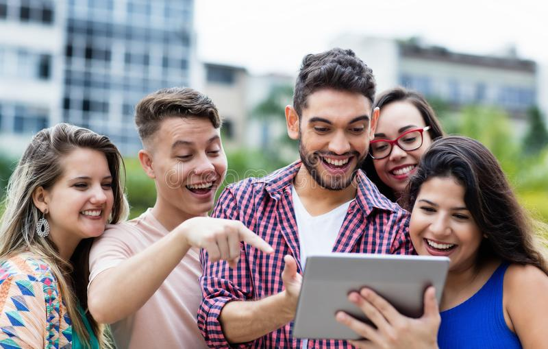 Spanish hipster student with tablet computer and group of cheering international students stock photos