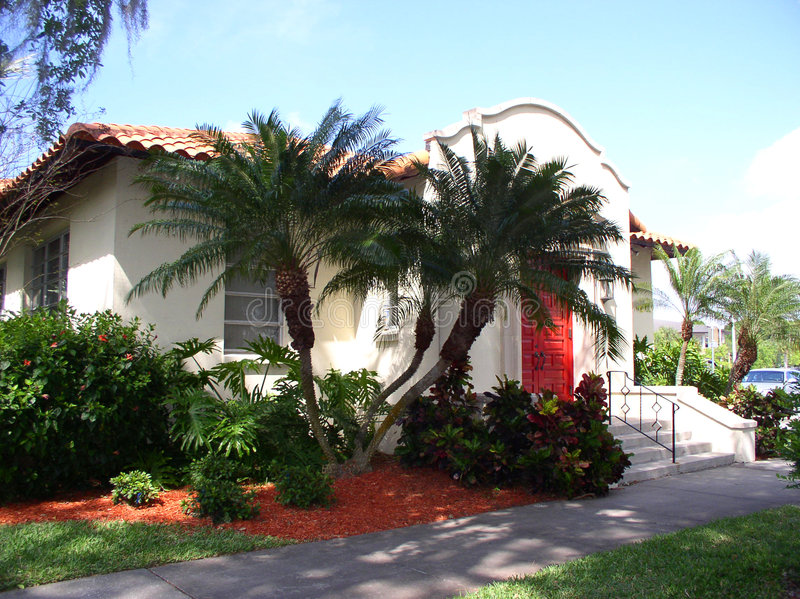 Spanish House. Little Spanish house in southwestern Florida, red tile roof, red door, surrounded by palm trees and other tropical greenery royalty free stock photography