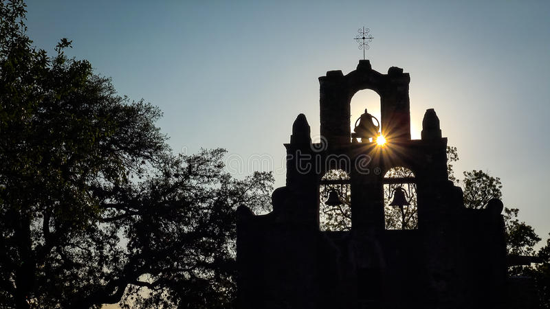 Spanish Mission Espada Church Bells in San Antonio, Texas. Spanish Mission Espada church bells in silhouette as the sun sets behind mission in San Antonio, Texas stock photography