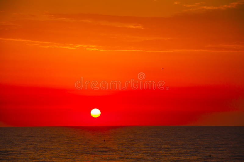 Spanish morning sun on red sky with yellow clouds by the Mediterranean sea stock photo