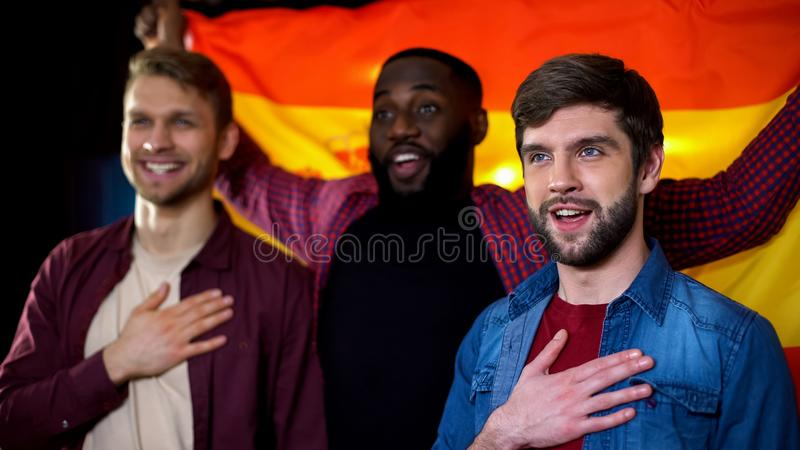 Spanish multiethnic male football fans singing national anthem and waving flag. Stock photo royalty free stock photo