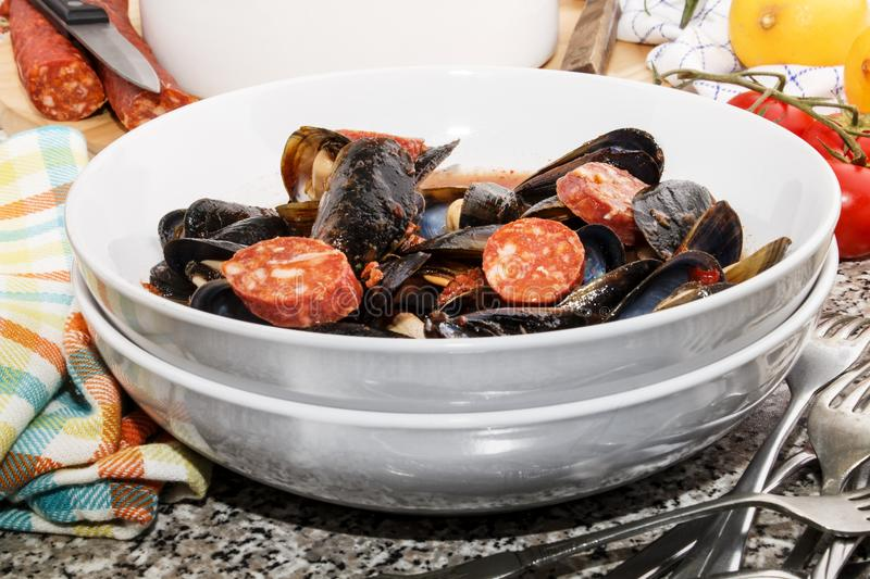Spanish mussel soup with sliced chorizo and tomato sauce stock photography