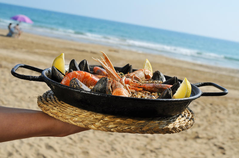 Spanish paella on the beach. A typical spanish paella with seafood in a paellera, the paella pan, on the beach stock image
