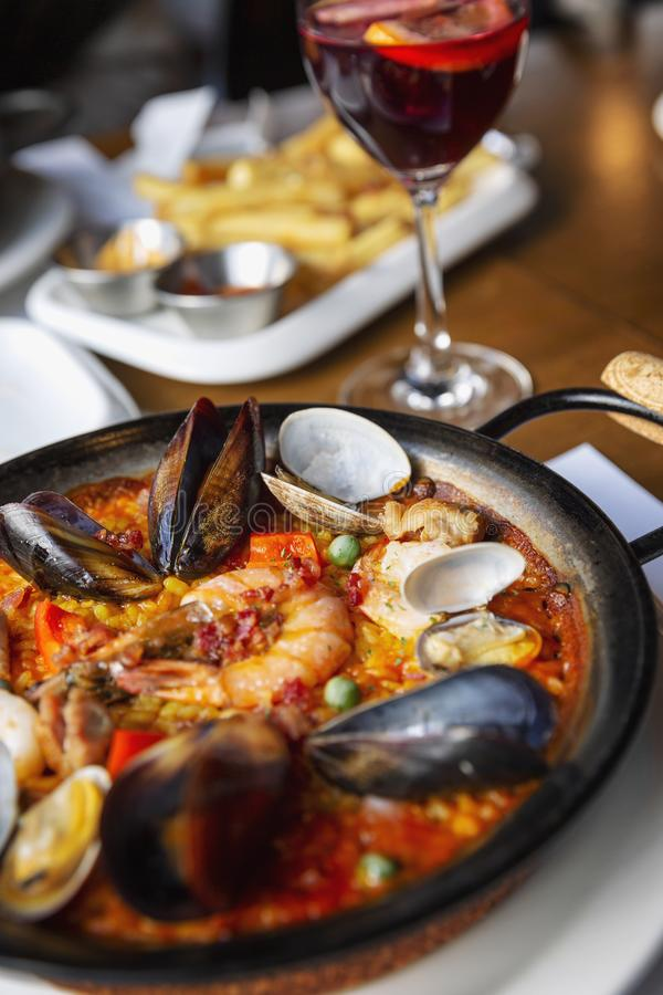 Spanish paella in a serving pan on a table in a cafe, close-up. Spanish paella and glass of wine in a serving pan on a table in a cafe, close-up royalty free stock photography