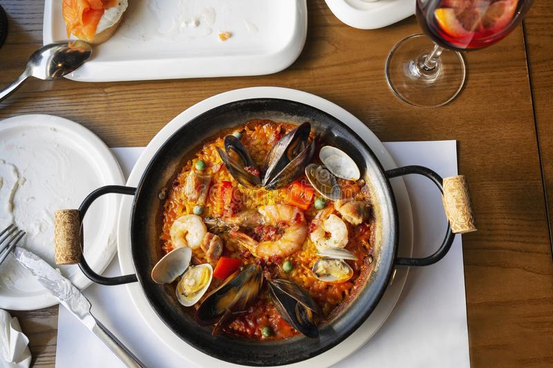 Spanish paella in a serving pan on a table in a cafe, close-up. Spanish paella and a glass of wine in a serving pan on a table in a cafe, close-up royalty free stock photos