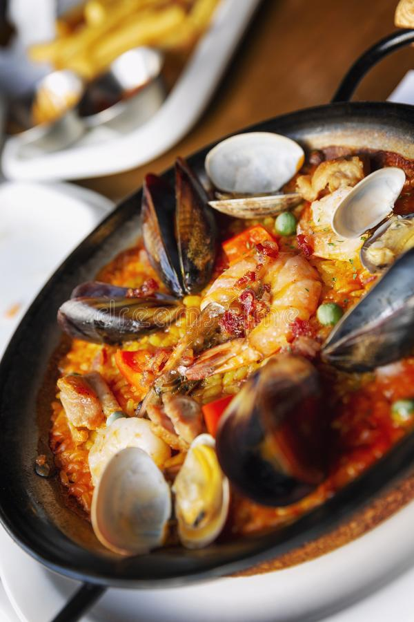 Spanish paella in a serving pan on a table in a cafe. Vertical royalty free stock photo