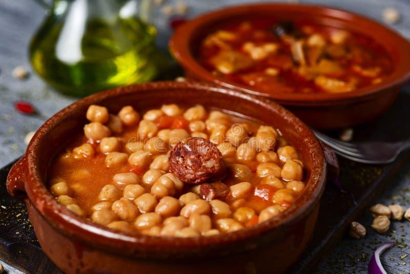 Spanish potaje de garbanzos and callos. Closeup of an earthenware bowl with potaje de garbanzos, a chickpeas stew with chorizo and serrano ham, and a bowl with royalty free stock images