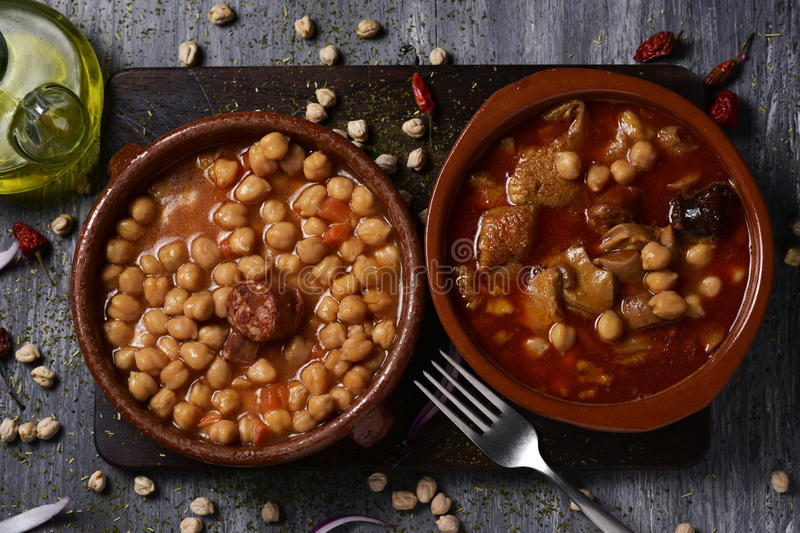 Spanish potaje de garbanzos and callos. High-angle shot of two earthenware bowls with two typical spanish dishes, potaje de garbanzos, a chickpeas stew with royalty free stock images