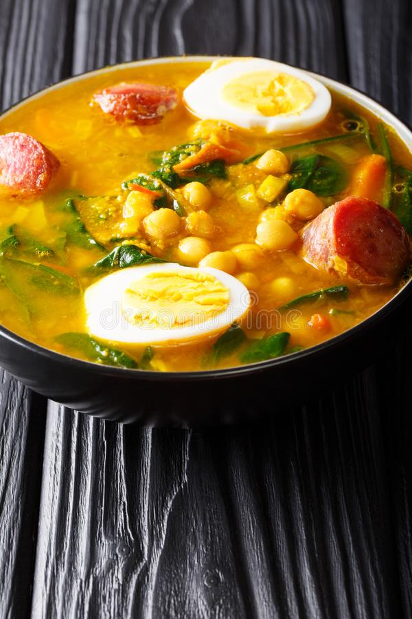 Spanish Potaje de vigilia con garbanzos spinach with chickpeas,. Sausages and eggs close-up in a bowl on the table. vertical stock images