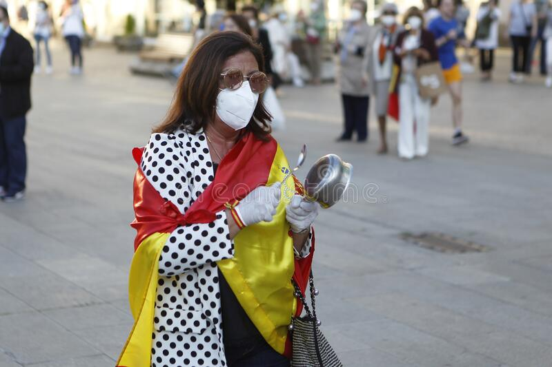 Spanish protester with face mask protesting touching a saucepan against the management of the government of Spain during the covid stock photography