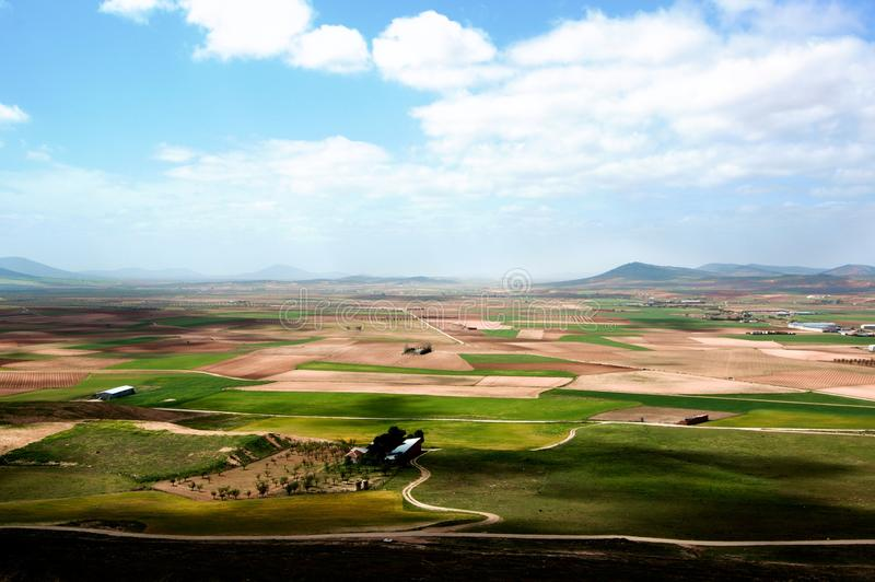 Spanish Rustic Landscape. With Green Grass and Yellow Clay Fields on Blue Sky and Hills Horizon in Sunny Day Outdoors. Consuegra, Spain royalty free stock images