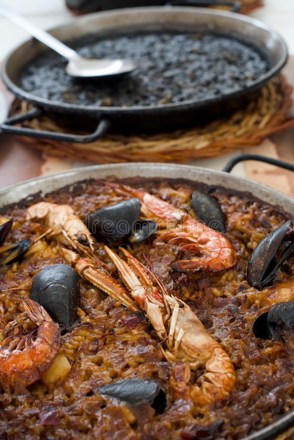 Spanish seafood paella and black paella royalty free stock photos