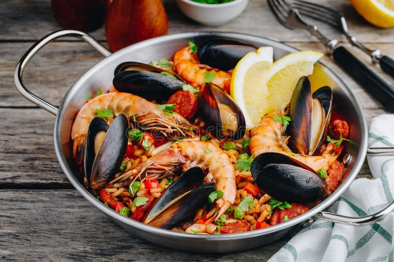 Spanish seafood paella with mussels, shrimps and chorizo sausages in traditional pan stock image