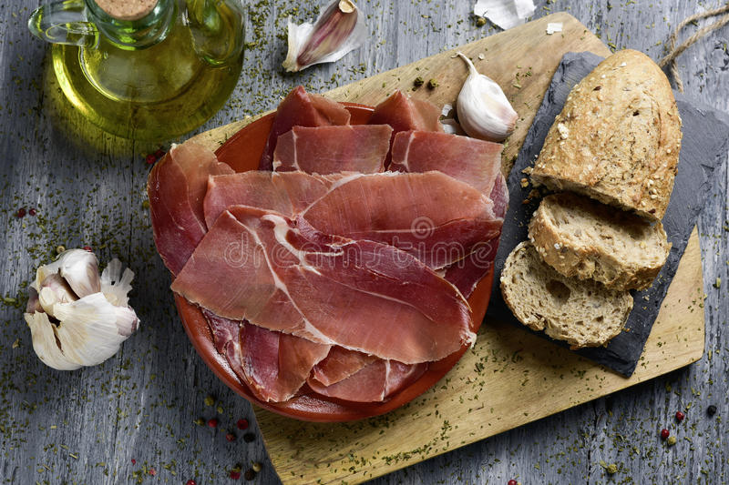 Spanish serrano ham. High-angle shot of an earthenware plate with some slices of spanish serrano ham, some slices of bread, a glass cruet with olive oil and some royalty free stock photography