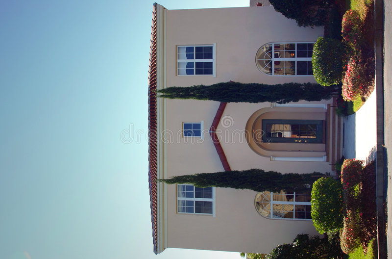 Spanish style home with tall trees at entrance stock image