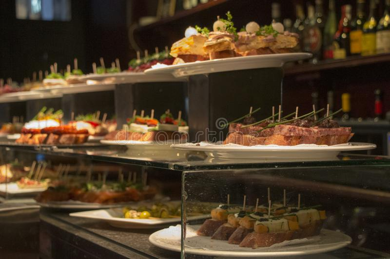 Counter filled with delicious tapas at a Spanish Tapas Bar. Traditional Bask Pintxos in a Tapas Bar in Barcelona, Spain stock images